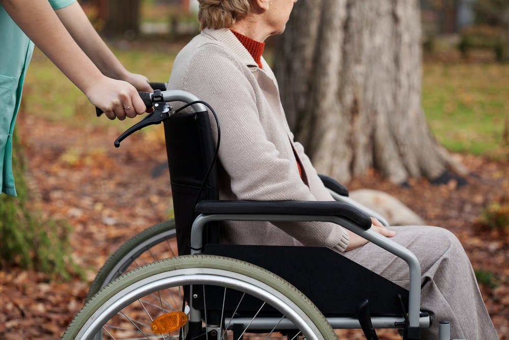 Disabled elder woman on wheelchair with nurse